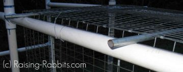 Close up of rabbit hutch plans - a cage suspended on a PVC rabbit hutch frame.