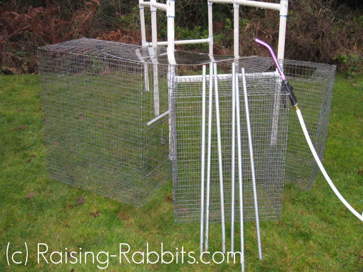 Cages and PVC rabbit hutch frame pulled outside and dismantled for cleaning.