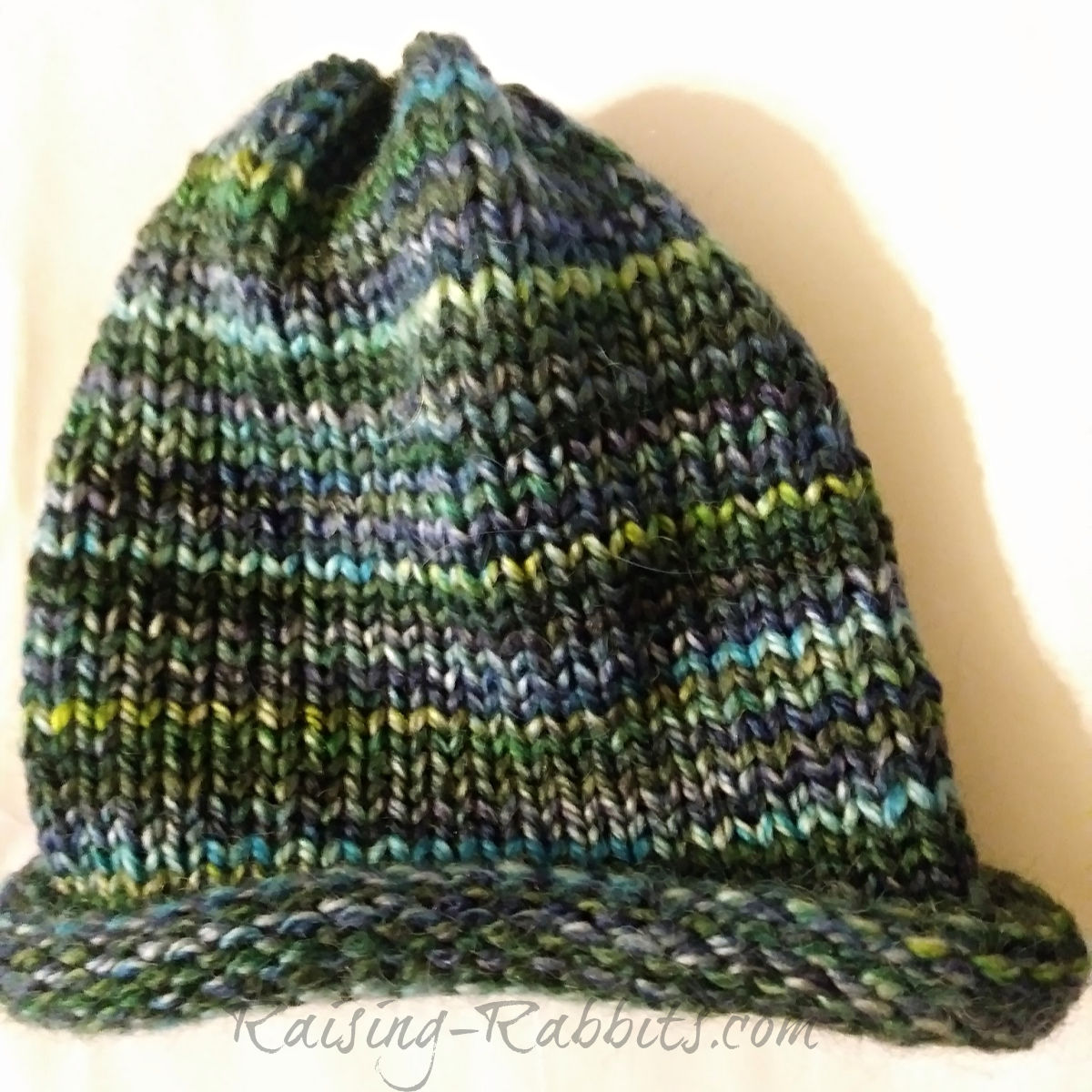 Green-turquoise-navy multi-colored beanie cap, one size fits all.